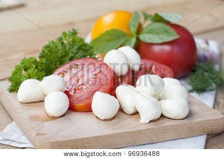 Sliced tomatoes, basil and mozzarella cheese on a wooden board