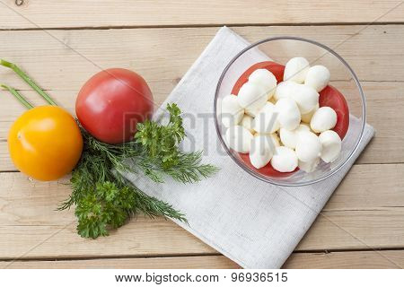 Mozzarella cheese in a glass bowl, tomatoes, sliced tomatoes and herbs on a wooden table