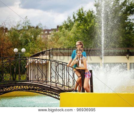 Best Friends Relaxing On A Bridge Near The Fountain.