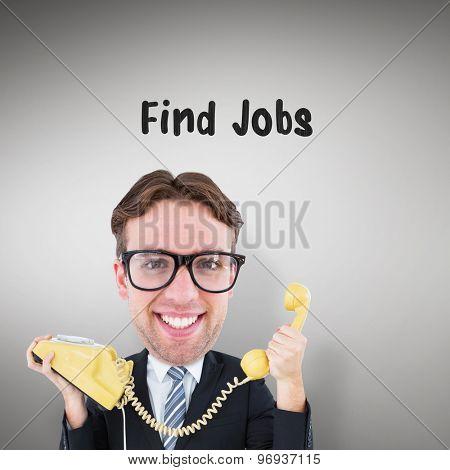 Geeky businessman holding phone against grey vignette