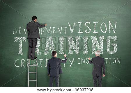 Business team writing against green chalkboard