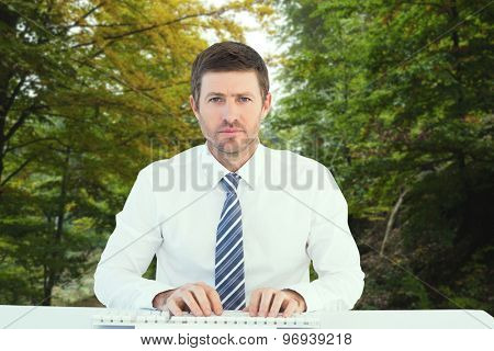 Businessman working at his desk against scenic shot of narrow road along forest