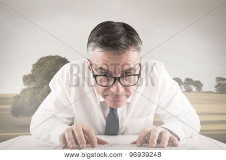 Mature businessman typing on keyboard against bright brown landscape