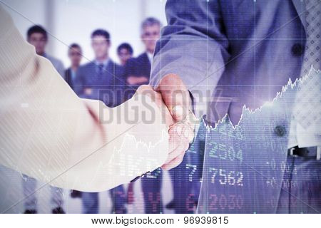 People in suit shaking hands against stocks and shares