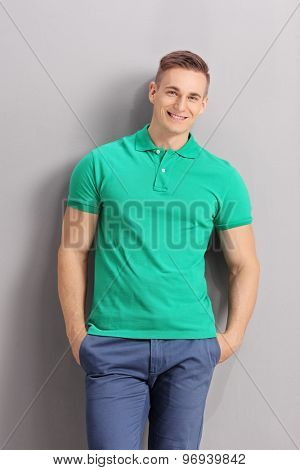Vertical shot of a cheerful young man in casual clothes leaning against a gray wall