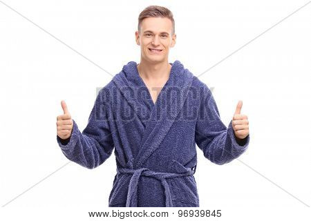 Young man in a blue bathrobe giving thumbs up and looking at the camera isolated on white background