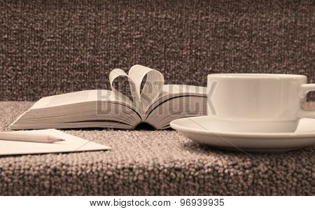 Pages Of Open Book Rolled In Heart Shape With Coffee On Table