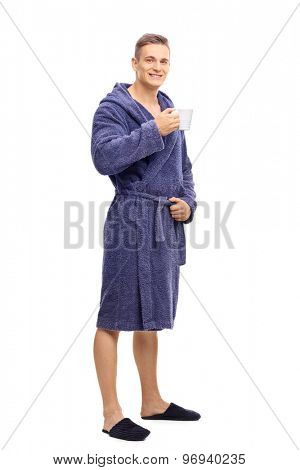 Full length portrait of a young man in blue bathrobe holding a cup of coffee and looking at the camera isolated on white background