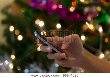 Hand Using Mobile Smart Phone With Colorful Light Celebration Background