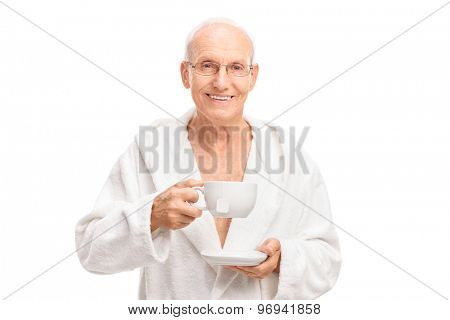 Cheerful senior in a white bathrobe holding a cup of tea and looking at the camera isolated on white background
