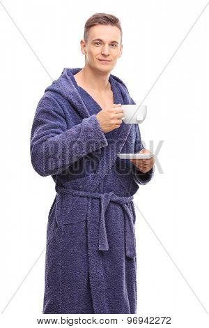 Vertical shot of a young man in a blue bathrobe drinking a cup of tea and looking at the camera isolated on white background