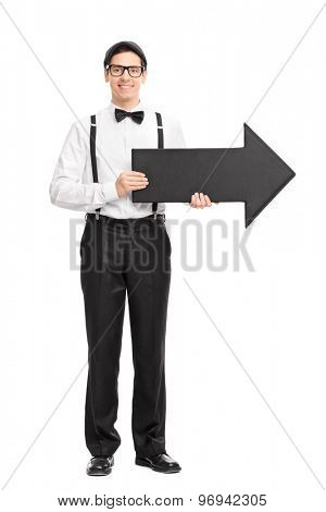 Full length portrait of a elegant young man with black bow-tie and suspenders holding a big black arrow pointing right isolated on white background