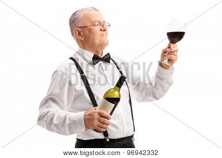 Elegant mature gentleman holding a bottle and a glass of fine red wine isolated on white background