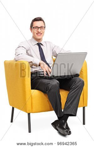 Vertical shot of a young cheerful businessman working on a laptop seated in a yellow armchair isolated on white background