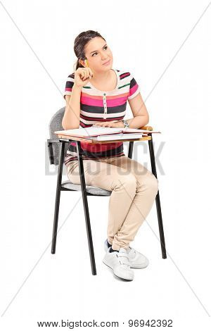 Vertical shot of a pensive female student sitting on a school desk and thinking isolated on white background