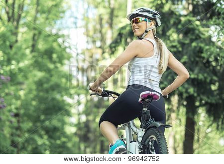 Portrait of beautiful woman on the bicycle in the park.
