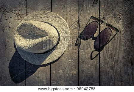 Sunglasses and hat on the wooden texture in sunday.