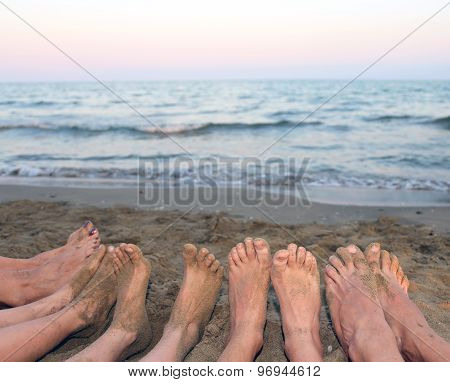 Feet Of A Family Barefoot By The Sea On The Beach In Summer
