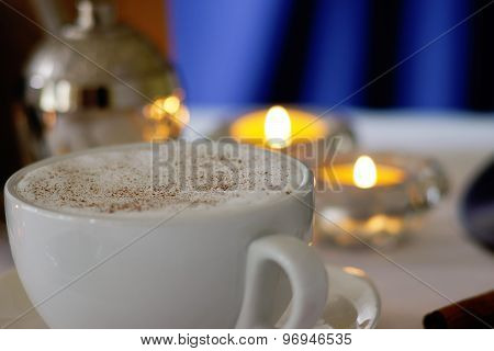 Coffee cup, coffee beans and candles on a white table