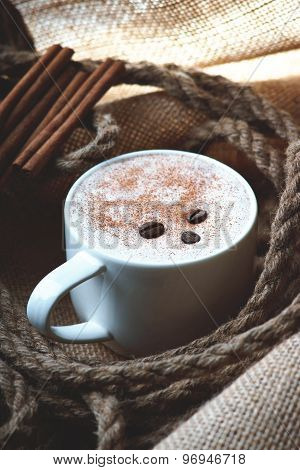 Cappuccino coffee cup,coffee beans, rope and cinnamon on burlap sack