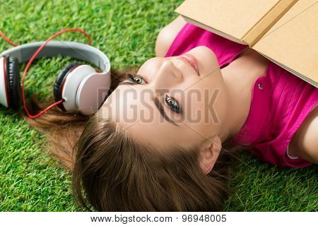 Young Beautiful Dreamy Woman Laying On Grass In The Park