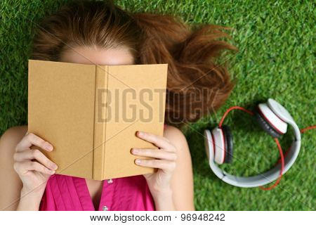 Young Beautiful Girl Laying On The Grass In Park Holding A Book