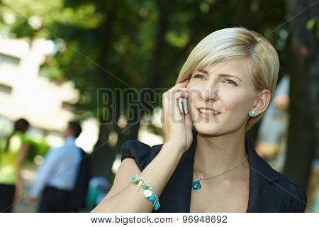 Young blonde caucasian businesswoman talking on mobile phone, outdoor. Smiling, standing.