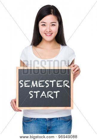 Student with chalkboard showing phrase of semester start