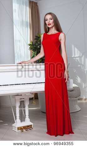 Beautiful brunette woman in a red dress. Studio shot. Long hair. Red lips.