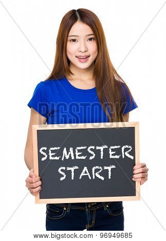 Young woman with black board showing phrase of semester start