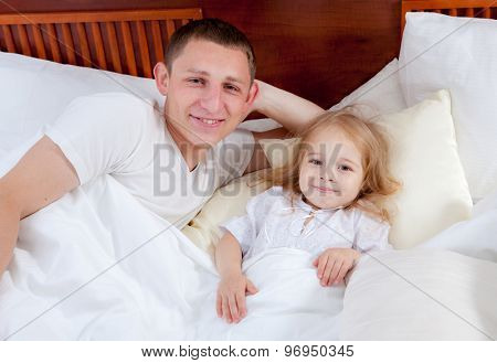 Happy family lying on a bed