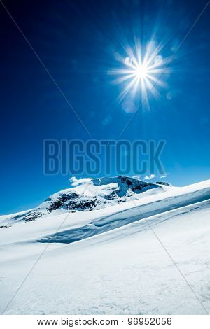 Sun in a blue sky over snowy mountain.