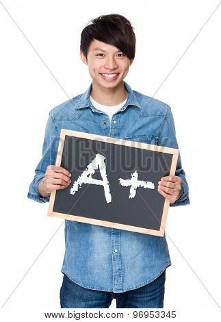 Asian young man with chalkboard showing A plus mark