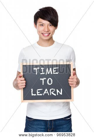 Young man hold with chalkboard showing phrase of time to learn