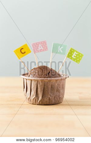 Chocolate muffins with small flag of a word cake
