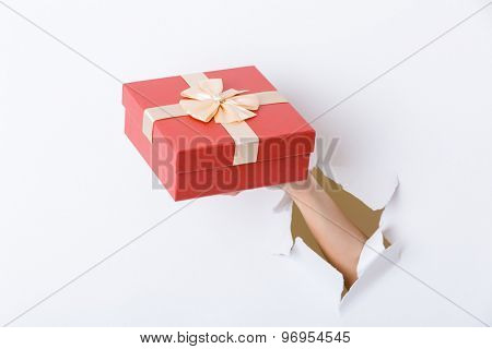 Hand holding giftbox through the hole in paper
