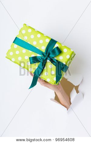 Hand breaking white paper showing gift box