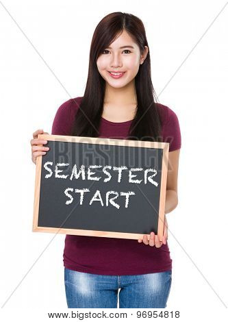 Asian woman with chalkboard showing semester start on board