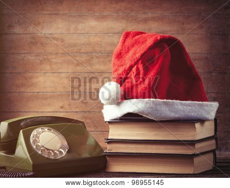 Santas Hat Over Books Near Green Dial Phone