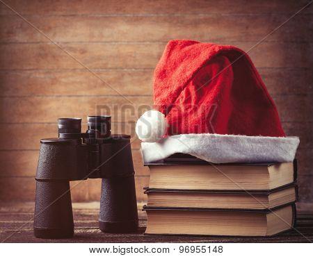 Santas Hat Over Books Near Black Binocular