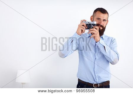 Young beard man holding a camera while standing against white background.