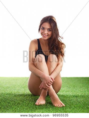 Woman sitting with crossed legs on the green grass .