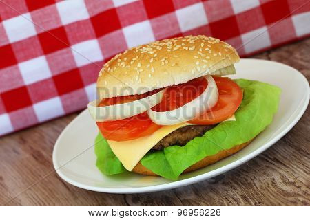Cheeseburger with red and white checkered cloth in the background