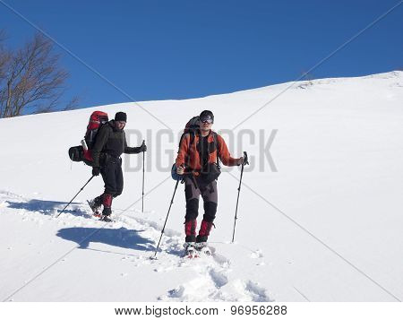 Men Go Snowshoeing In The Mountains In The Snow.