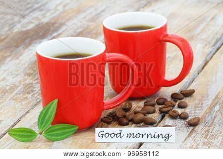 Good morning card with two mugs of coffee with coffee beans scattered on rustic wooden surface
