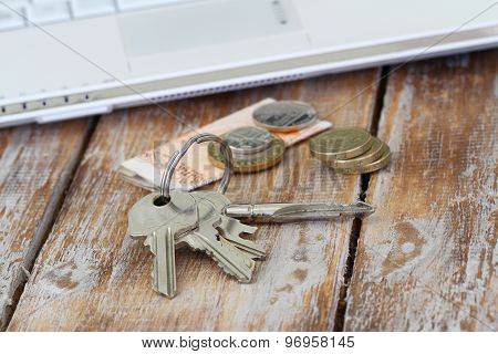 Bunch of keys on rustic surface and some change in British pounds