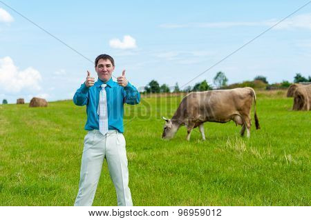 young businessman showing thumbs up in the background of green grass and cows