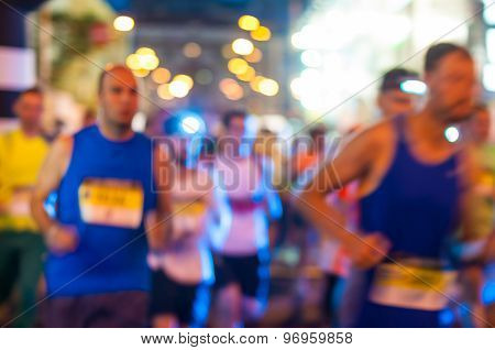 Blurred Runner shortly after the start at night run.  Bokeh background
