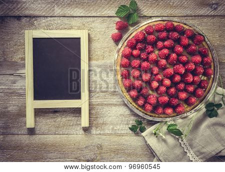 Tart with raspberries on a wooden background with a chalk board for recipe. top view