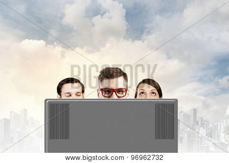 Young people looking out above laptop monitor